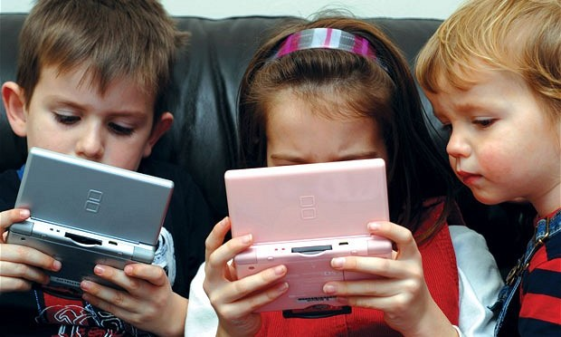 Kids with their noses in electronic devices.